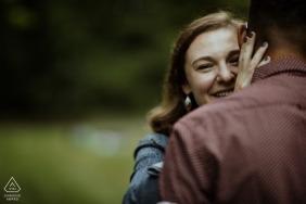 Boston, MA Engagement Shoot - Ella mira por encima de su hombro durante un abrazo en su sesión en Jamaica Pond