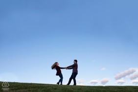 Millcreek Ravine, Edmonton Engagement Photography: Couple twirls at top of hill