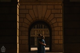 University of Birmingham, Edgbaston, UK engagement photography | A couple, facing into the sunlight, embrace at the university where they first met.