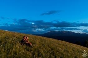 林地公园订婚肖像—夫妇在草地上,矛峰在背景中。