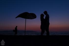 Güzelçamlı Kuşadası, Türkei Portrait Session vor der Hochzeit - Silhouette des Paares und ein Sonnenschirm am Strand mit einem Fischer, der dahinter vorbeigeht