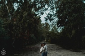 Engagement Photography in Naples standing on a path surrounded by trees
