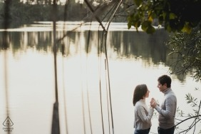 Naples wedding photographer image of an engaged couple holding hands by a lake