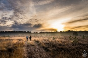 Engaged couple walking on the moor during photo shoot in Rucphense Heide, Rucphen