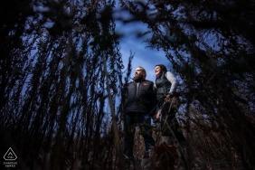 Minnesota-Verlobungssitzung in Silverwood Park - Paar im hohen Gras mit einem blauen Himmel hinter ihnen