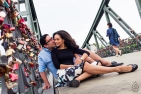 Frankfurt - Eiserner Steg Verlobungssitzung - Paar am Eisernen Steg sitzt neben Vorhängeschlössern