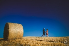 Engagement Photo Session in Crete Senesi, Tuscany - round hay bale, field, holding hands