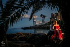 Cascais, Portugal Engagement Photo of a Couple - Portrait contains: last light, red dress, palm trees, blue sky