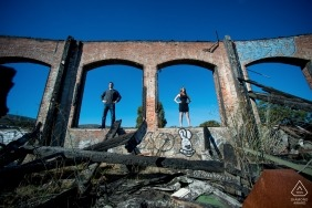 San Francisco, California Couple stands in the windows of a burned-out building. Engagement Photography - Portrait contains: CA, windows, ashes, remains