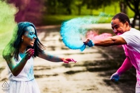Germany Couple throwing powder on each other | Engagement Photo Session - Portrait contains: green, blue, pink, laughing, fun, together, smiles