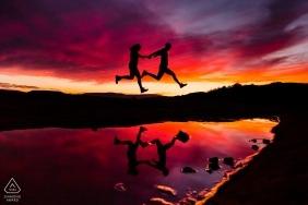 Los Angeles Engagement Silhouette Photography - Couple sautant au-dessus de l'eau avec un ciel rouge