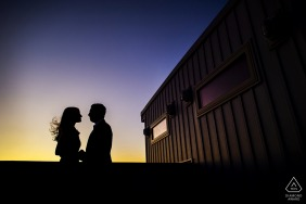 Future bride and groom share a hug in Philadelphia. - PA silhouette, dark, sunset, wind, hair, blowing