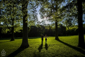 Future bride and groom walk along Holmdel Park in Holmdel, NJ | Engagement Couple Portrait - Image contains: park, woods, shadows, grass, blue sky