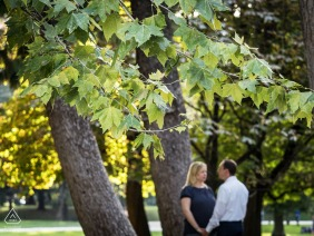 Milano, Italy engagement photography - Couple out of focus near the trees.