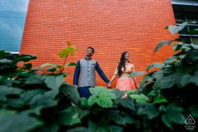 University of Alberta, Edmonton, AB, Canada - holding the hands - Engagement Photography - Portrait contains: brick, wall, bushes, ivy, holding, hands, urban
