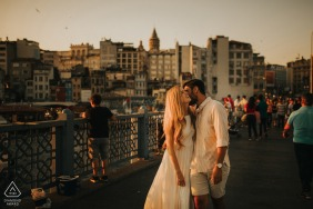 A couple holding each other and smiling on Galata Bridge during their engagement picture session.
