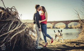 Bolano Love engagement photo shoot with a couple kissing and a running dog