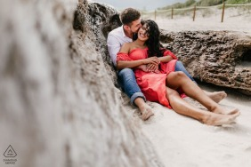 Retrato em South Pointe Park, South Beach, FL sessão de fotos de noivado com um casal sentado na areia.