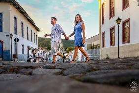 Cidade de Goiás Engagement Portraits - Image contains: couple, walking, stones, buildings, sky, village
