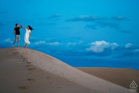 Glamis, Ca Couple dances on the sand dunes during engagement photo session in the desert
