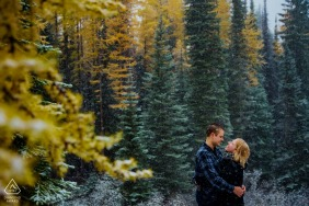 Engagement Photography - Rossland BC Couple snuggles as the snow falls among larch trees in autumn