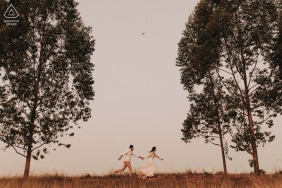 Mateus Leme, Minas Gerais / Brasil couple running in the field between the trees during engagement shoot.