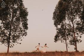 Mateus Leme, Minas Gerais / Brasil-Paare, die auf dem Gebiet zwischen den Bäumen während des Verlobungsschießens laufen.