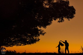 Cedro do Abaeté, Minas Gerais, Brazil | Engagement silhouette portraits at sunset of a couple spinning while dancing.