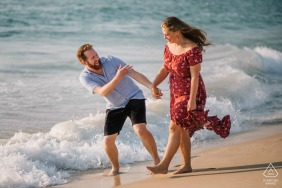 Perth couple Walking and laughing together at the beach during engagement portrait session.