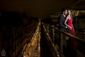 Barcelona Couple enjoying each other leaning on a balcony with a busy street below them - Engagement Session