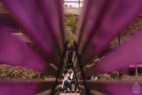 Barbican Centre, London engagement photoshoot | Couple having a chat - shot through a park bench to frame the couple