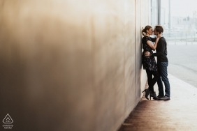 Couple Shoot in the middle of Düsseldorf against a clean, plain wall, with a kiss
