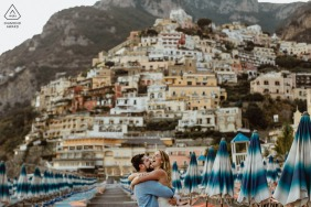 Couple laughing in front of the Positano mountains during engagement photo session.