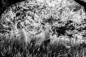 Campinas - São Paulo couple walk on the gress in a black and white photo session for engagment portraits