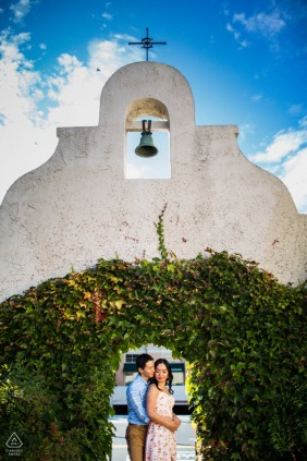 Los Gatos engagement photo shoot of a couple hugging under a mission bell