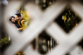 Southern California engaged couple portrait shot through lattice fencing.