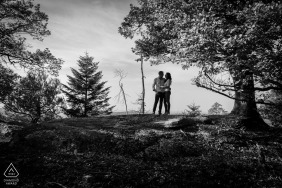 Black and white engagement picture of a couple under a tree in the Saverne forest