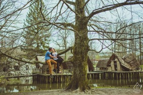 Couple sitting on the tree in the Bally Park during a pre-wed portrait session.