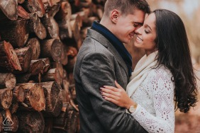 Rio Grade do Sul engagement shoot of a couple holding each other near a stacked wood pile.