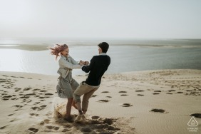 Charente-Maritime engagement image - Dancing and spinning couple in the beach sand.