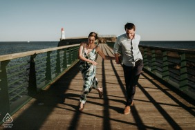 Nouvelle-Aquitaine couple picture - Running on the boardwalk pier having fun.
