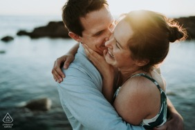 Charente-Maritime engagement hug and a kiss by the water with sun flare.