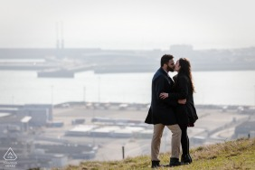 White Cliffs of Dover, Kent, UK pre-wedding picture - A newly engaged couple embrace with the port in the distance
