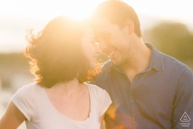 Backlit photo of a loving couple touching heads at sunset in Paris during an engagement session