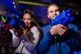 Engagement Photographer | Dave and Busters, Anne Arundel, Maryland -  playing video games engagement session. This photo shows them playing a shooting game