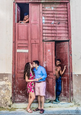 Couple Engagement Photo Session | A couple stop for a kiss while exploring a Havana neighborhood