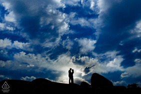 Engagement Photo from Lake Tahoe, CA - Small, silhouetted man and woman standing on rocks in front of a dark blue, cloudy sky.