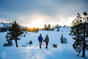 Engagement Sessions | Lake Tahoe, CA - Man and woman walking towards the sunset in a snowy, mountain landscape.