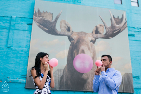 Engaged Couples Photography | Image of couple with a mural in Chicago's South Loop with a moose blowing a bubble