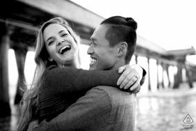Verlobungsfotografie-Sitzung von Marina Del Ray - Paar, das am Strand in Schwarzweiß lacht